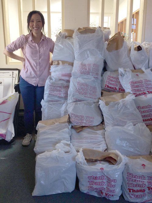 A volunteer stands next to packed groceries.