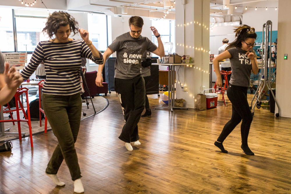 Participants are dancing in their socks during a work break.